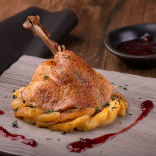 Confit de pato con manzana caramelizada y salsa de frutos rojos